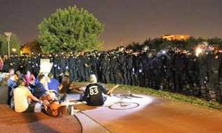 Riot police surround seated demonstrators
